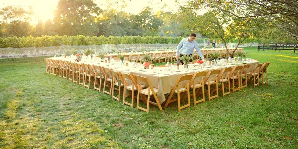 caterer arranging tables for a large outdoor party